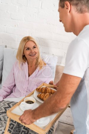 Photo for Man giving breakfast tray with croissants and coffee to smiling wife in bed - Royalty Free Image