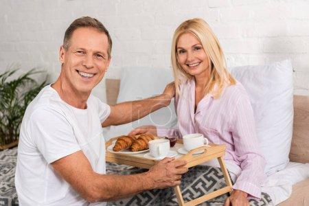 Couple souriant à la caméra tout en prenant le petit déjeuner au lit