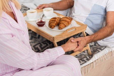 Photo pour Vue en dents de scie d'un couple tenant les mains pendant le petit déjeuner au lit - image libre de droit