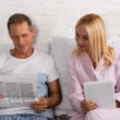 Mature couple reading newspaper and using digital ...