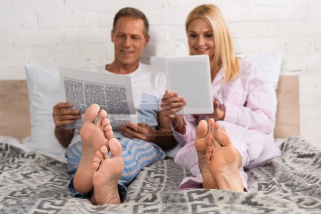 Photo for Man reading newspaper while wife using digital tablet on bed - Royalty Free Image