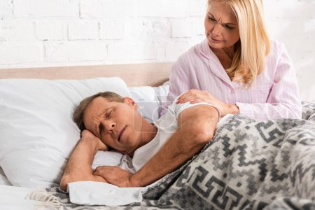 Photo for Worried woman waking up snoring husband in bed - Royalty Free Image