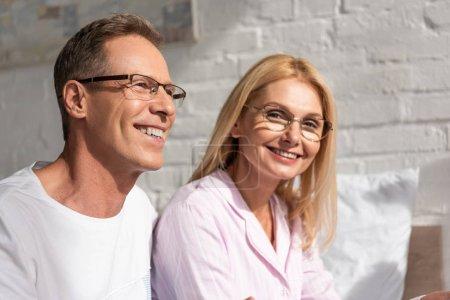Photo pour Couple souriant dans des pyjamas et des lunettes assis sur le lit le matin - image libre de droit