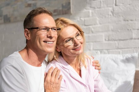 Photo pour Un homme souriant serrant sa femme dans un pyjama au lit le matin - image libre de droit