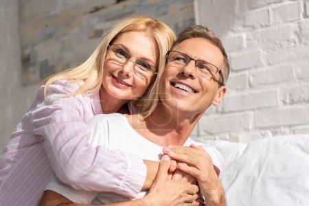 Photo pour Couple souriant en pyjamas et lunettes serrant dans sa chambre le matin - image libre de droit