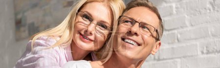 Photo for Panoramic shot of smiling couple in eyeglasses hugging at home - Royalty Free Image