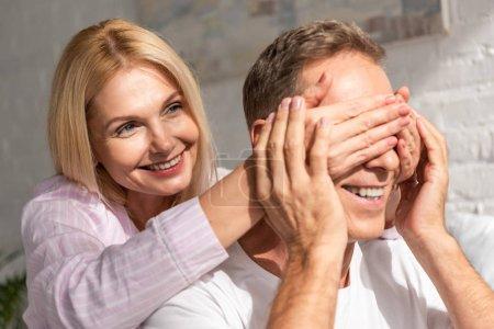 Photo pour Une femme souriante couvrant le visage de son mari des mains à la maison - image libre de droit