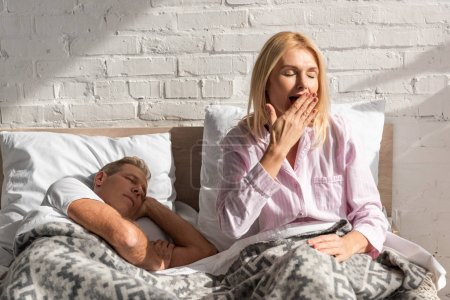 Photo for Woman yawning beside sleeping husband in bed - Royalty Free Image