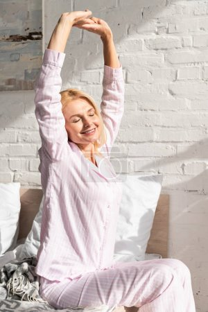 Photo for Smiling woman waking up and stretching in bed at morning - Royalty Free Image