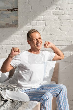 Photo for Smiling man waking up and stretching in bed at morning - Royalty Free Image