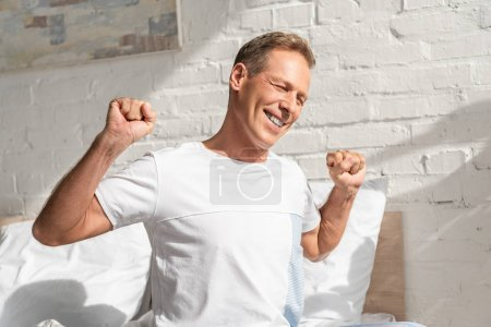 Photo for Smiling man stretching while sitting on bed at morning - Royalty Free Image