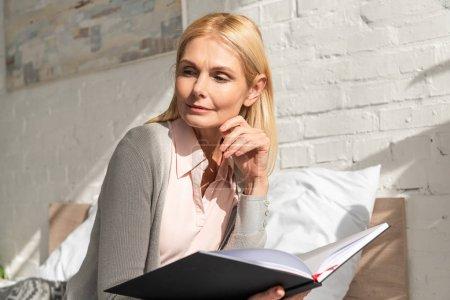 Photo pour Femme pensive avec carnet de notes assise sur le lit - image libre de droit