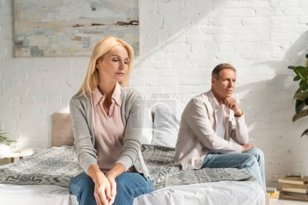 Photo for Worried couple sitting on bed and looking away - Royalty Free Image
