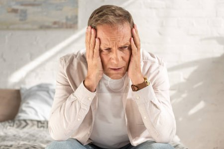 Photo for Disappointed man with hands near head sitting on bed - Royalty Free Image