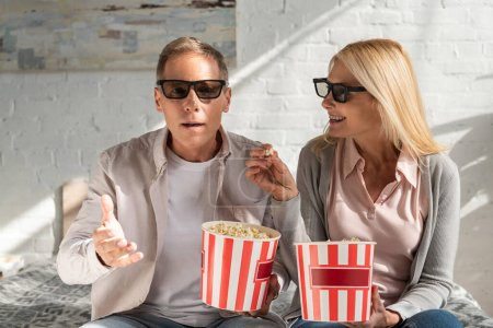 Photo for Mature couple in 3d glasses holding buckets with popcorn on bed - Royalty Free Image