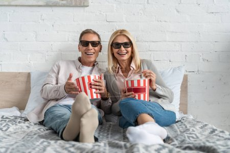 Photo for Smiling couple in 3d glasses with popcorn buckets on bed - Royalty Free Image