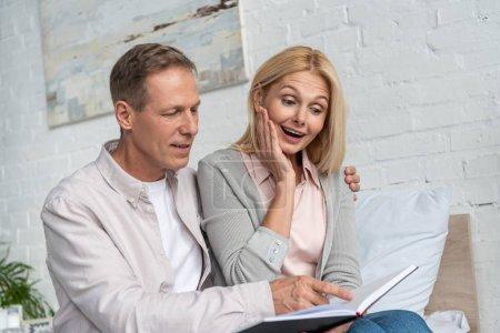 Photo pour Un homme se dirige vers un carnet pour choquer sa femme au lit - image libre de droit