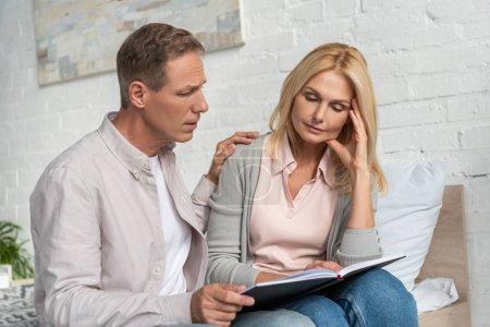 Photo pour Un homme calme une femme attentionnée avec un carnet au lit - image libre de droit