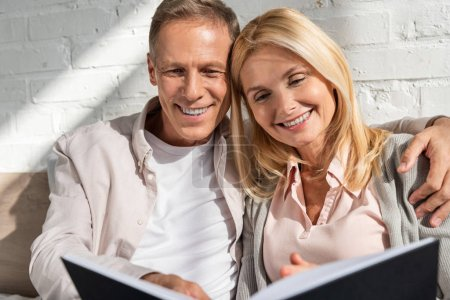 Photo for Smiling couple looking at notebook and man embracing wife - Royalty Free Image