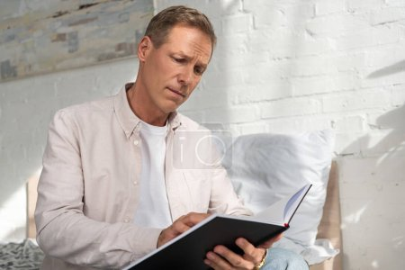 Photo for Worried man looking in notebook while sitting on bed - Royalty Free Image