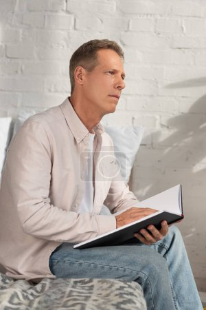 Photo for Thoughtful man holding notebook and looking away on bed - Royalty Free Image