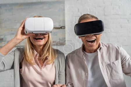 Photo for Laughing couple in virtual reality headsets at home - Royalty Free Image