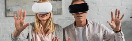 Photo for Panoramic shot of couple using virtual reality headsets at home - Royalty Free Image