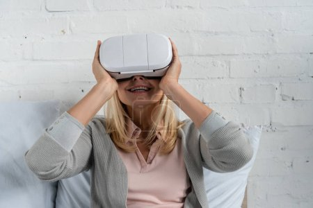 Photo for Smiling woman using virtual reality headset on bed - Royalty Free Image