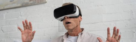 Photo for Panoramic shot of exited man in virtual reality headset at home - Royalty Free Image
