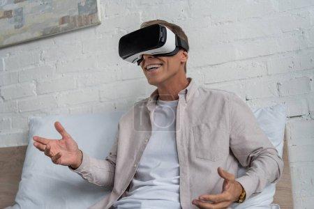 Photo pour Un homme souriant dans un casque de réalité virtuelle jouant à un jeu vidéo au lit - image libre de droit