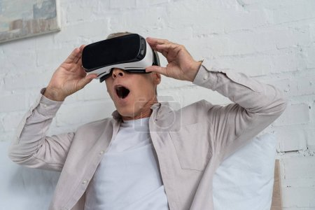 Photo for Shocked man in virtual reality headset playing video game on bed - Royalty Free Image