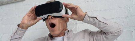 Shocked man in virtual reality headset playing video game, panoramic shot