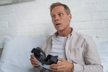 """Photo pour Un homme choqué tenant un casque d """"écoute de réalité virtuelle au lit - image libre de droit"""