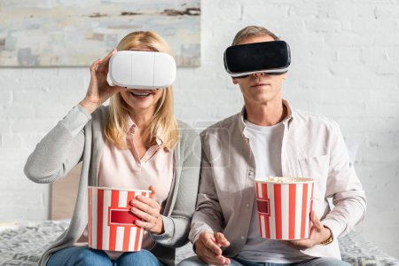 Photo for Coupe in virtual reality headsets holding popcorn on bed - Royalty Free Image