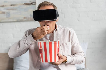 """Photo pour Homme en réalité virtuelle casque d """"écoute mangeant du maïs soufflé au lit - image libre de droit"""