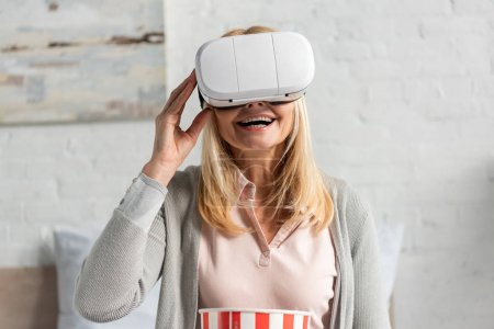 Exited woman in virtual reality headset with popcorn on bed