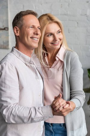 Photo pour Smiling mature couple holding hands and dancing at home - image libre de droit