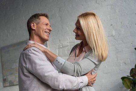 Photo pour Un couple mature souriant dansant dans un salon - image libre de droit