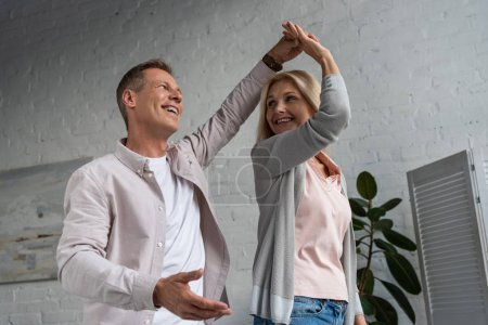 Photo pour Mature couple smiling to each other while dancing in living room - image libre de droit