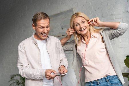 Un homme souriant tenant un smartphone tandis que sa femme écoutait de la musique avec des écouteurs dans le salon