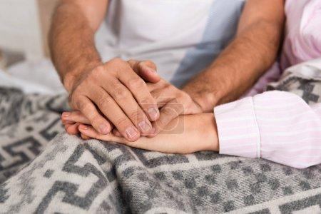 Photo pour Vue croustillante d'un couple tenant la main sur une couverture dans son lit - image libre de droit