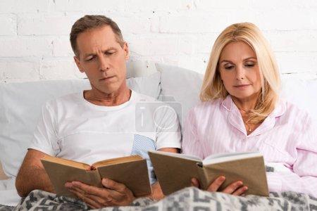 Photo pour Couple dans un pyjama lisant des livres au lit - image libre de droit