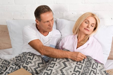 Photo for Man covering with blanket sleeping wife in bed - Royalty Free Image