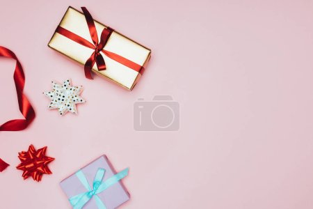 top view of christmas gift boxes with ribbons and bows, isolated on pink