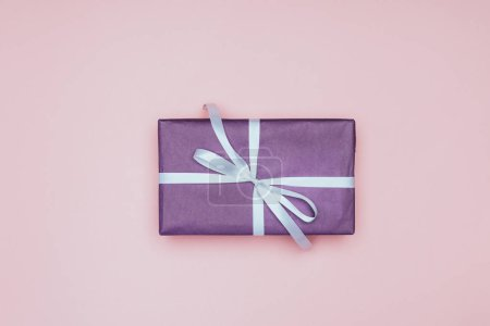 Photo for Top view of purple christmas present with ribbon, isolated on pink - Royalty Free Image