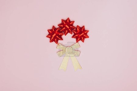 top view of red and golden bows isolated on pink