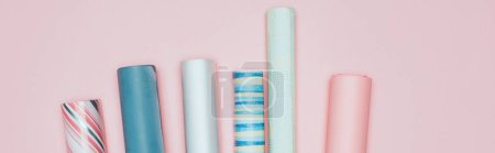 panoramic shot of wrapping paper rolls on pink