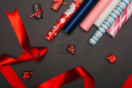 Photo pour Vue du dessus des rouleaux de papier d'emballage, ruban et petites boîtes-cadeaux sur noir - image libre de droit