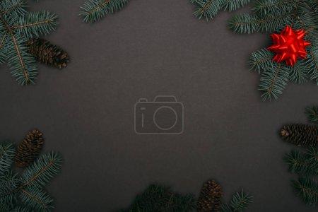 Foto de Vista superior del marco de las christmas con ramas de abeja, conos de pino y arco rojo sobre negro. - Imagen libre de derechos