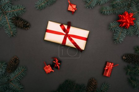 Photo pour Top vue des boîtes cadeaux de Noël avec branches d'épinette et cônes de pin sur fond noir - image libre de droit